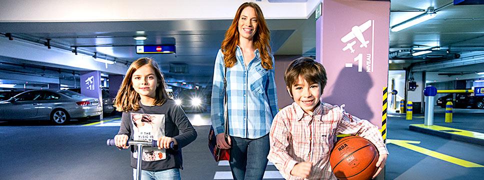 Lächelnde Mutter mit zwei Kindern im Parkhaus