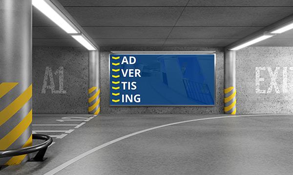 """Große Werbetafel mit Schriftzug """"Advertising"""" an einer Wand im Parkhaus"""