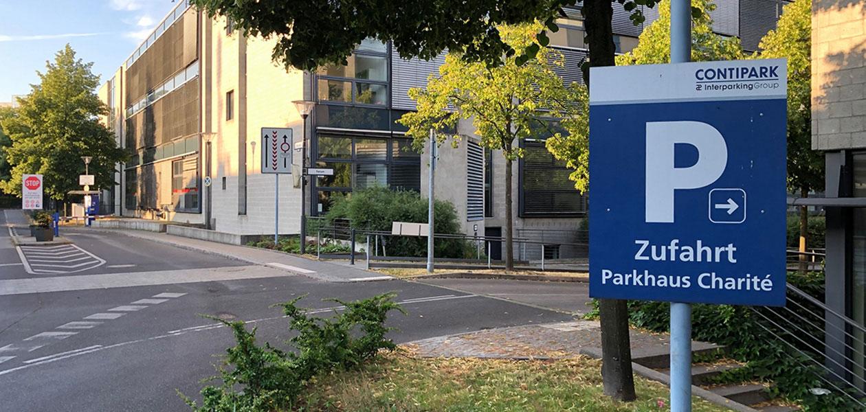 """Hinweisschild mit Schriftzug """"Zufahrt Parkhaus Charité"""" vor einem Gebäude"""