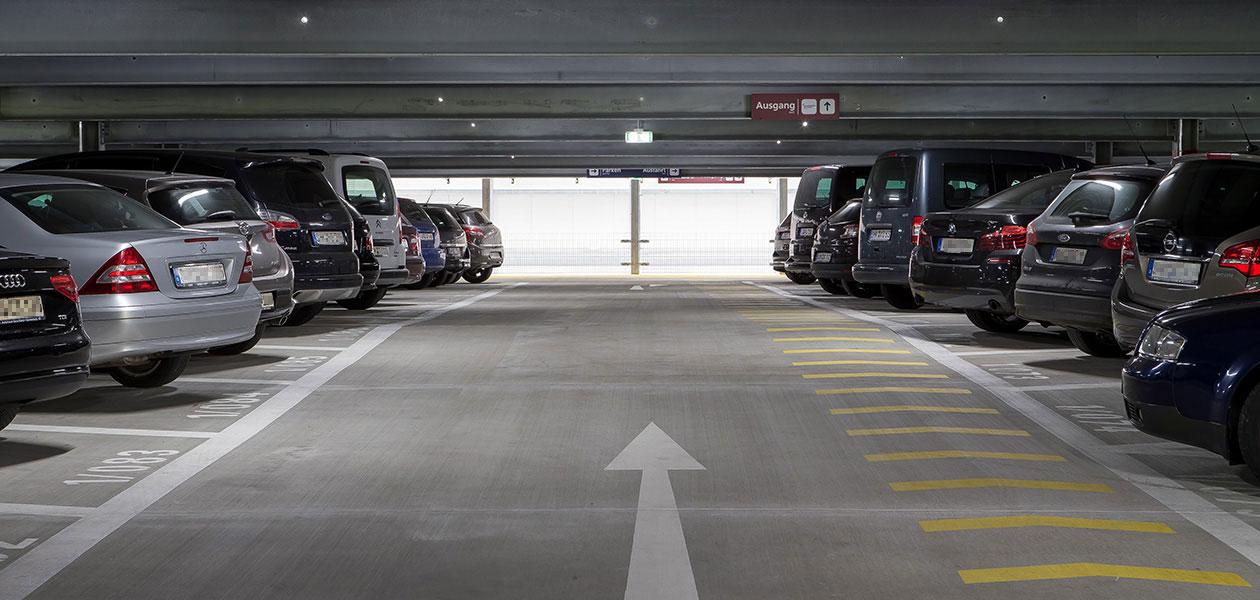 Gasse im Parkhaus mit parkenden Autos links und rechts