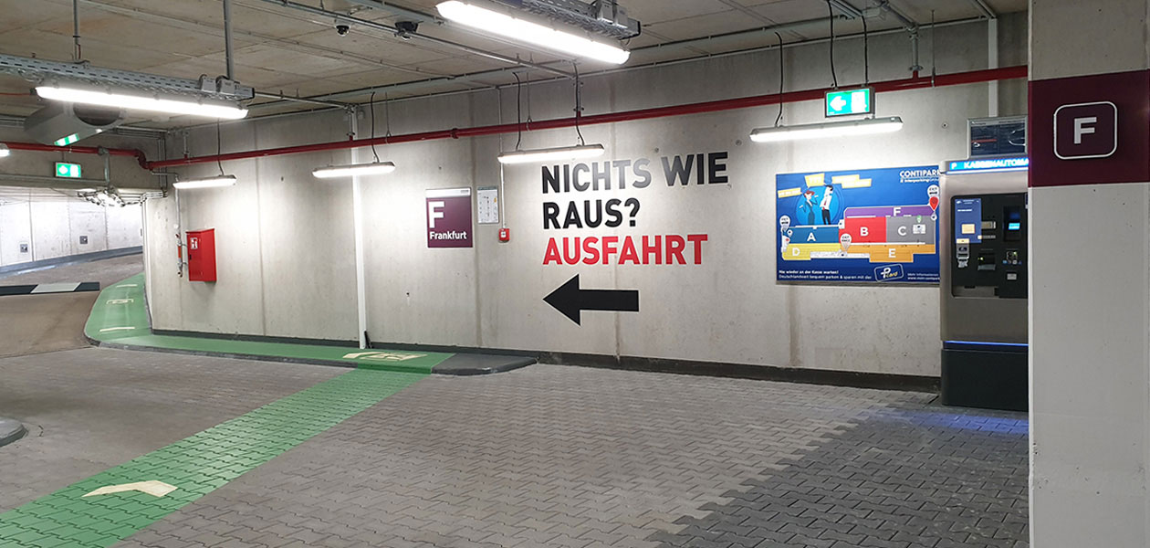 "Schriftzug ""Nichts wie raus? Ausfahrt"" mit Pfeil in Richtung Ausfahrt an der Parkhauswand"
