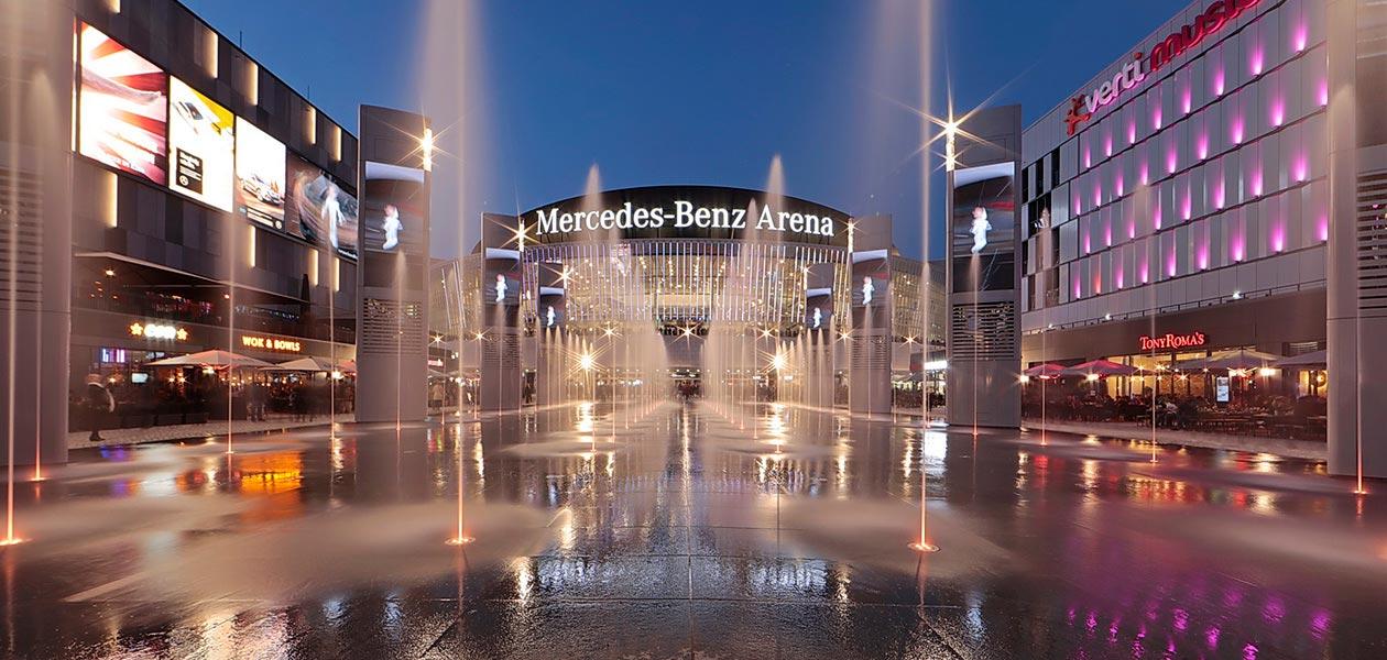 Blick über den beleuchteten Vorplatz zur Mercedes Benz Arena in Berlin in der Dämmerung